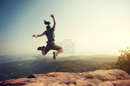 woman jumping on mountain peak