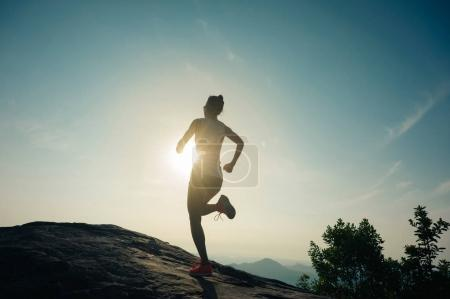 Photo for Sporty young woman running at mountain top - Royalty Free Image