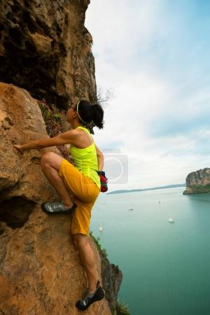 woman climbing at seaside cliff