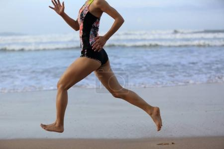 young woman running on sandy beach