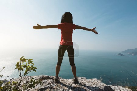 young woman standing with outstretched arms on sunrise windy coast