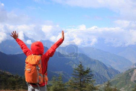 happy woman backpacker standing on mountain peak