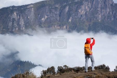 Young woman backpacker taking selfie on mountain peak