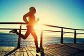 sporty young woman running on seaside boardwalk during sunrise