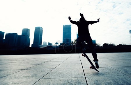 Skateboarder doing a trick named ollie in city park with skateboard