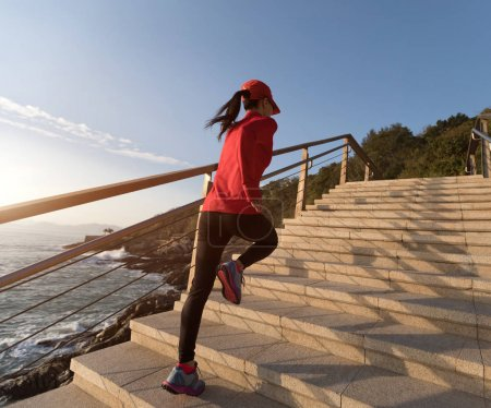 sporty fitness woman running upstairs on coast trail