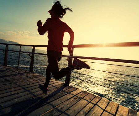 sporty young woman running on seaside boardwalk