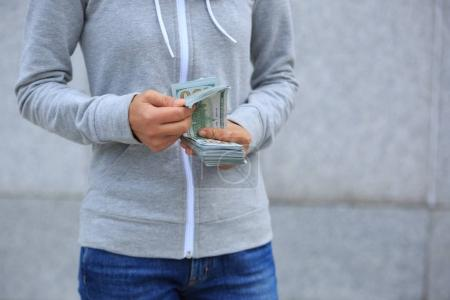 Female hands counting money on blurred city background