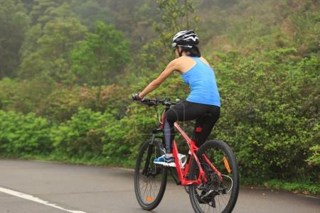 Young woman cyclist riding mountain bike on trail