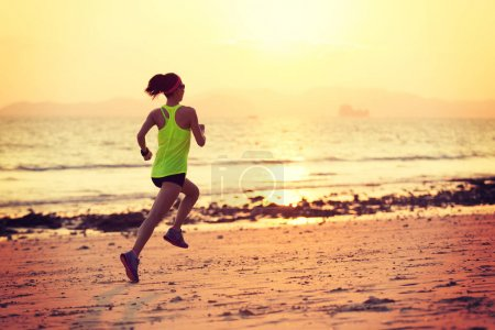 young woman jogging on shore during sunrise