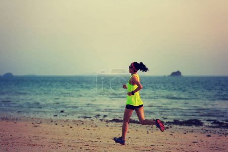 Side view of sporty young woman jogging on shore