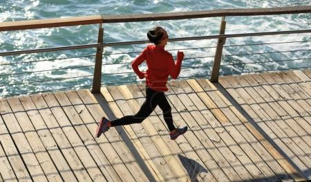 sporty fitness young woman running on seaside boardwalk