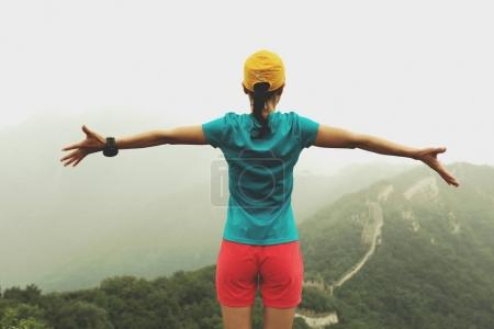 successful woman hiker with open arms to the great wall on the top of mountain