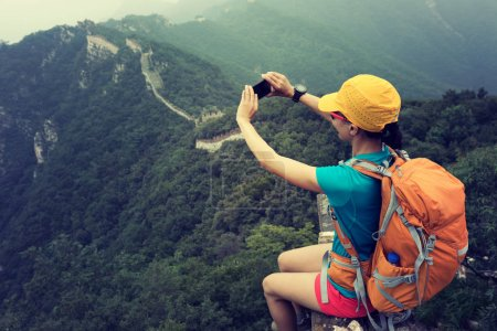 young woman hiker taking photo with smartphone on top of great wall