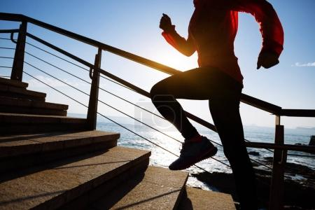 sporty fitness woman running upstairs at coast trail