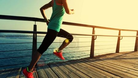sporty fitness female runner running on seaside boardwalk during sunrise