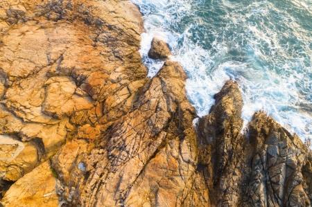 aerial view of sea wave break on the coast rocks