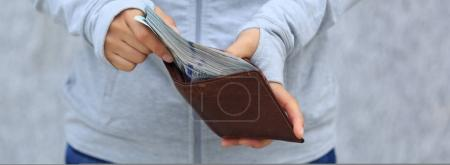 Female hand put money into wallet on blurred city background