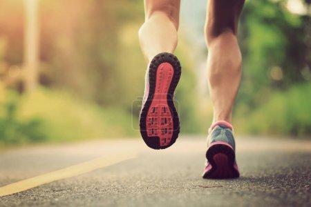 fitness female trail runner running in the forest