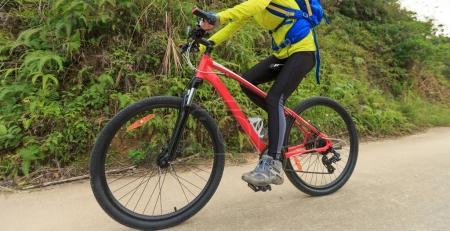 Photo pour Cycliste féminine CIRC. VTT sur sentier forestier - image libre de droit