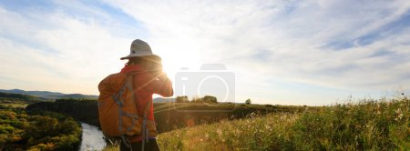 young woman photographer taking photo on sunset mountain top