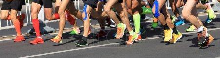 Photo pour Jambes de coureur de marathon en cours d'exécution sur la route de la ville - image libre de droit