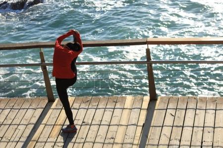 sporty fitness female warming up stretching legs on seaside boardwalk