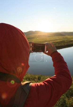 Tourist taking photo with smartphone in beautiful sunset landscape