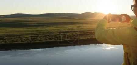 Woman taking photo with smartphone of beautiful sunset landscape