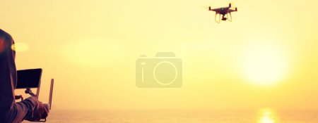 woman holding remote control of flying drone which taking photo over sunrise sea
