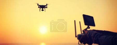 Photo for Woman holding remote control of flying drone which taking photo over sunrise sea - Royalty Free Image