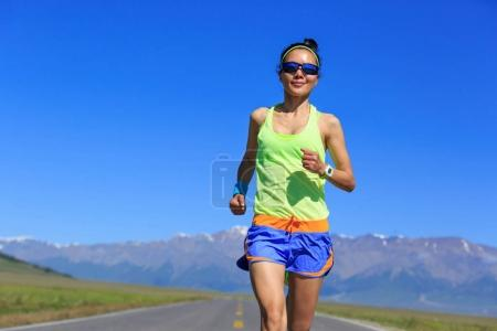 Young fitness healthy lifestyle woman runner running on road with snow capped mountains on background
