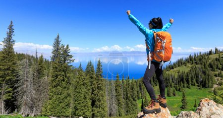 successful Hiker with outstretched arms standing at cliff edge on mountain top