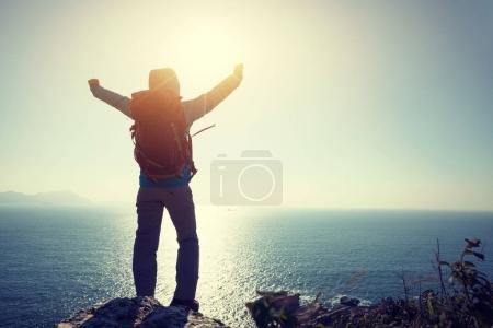 successful female hiker standing on sunrise seaside mountain cliff