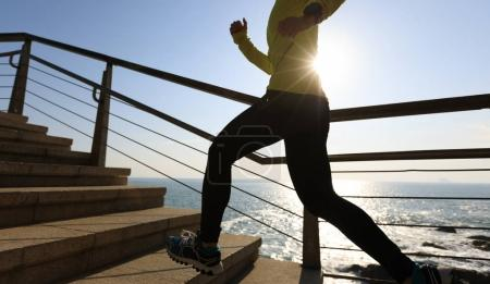 sporty female jogger running on seaside stairs during sunrise