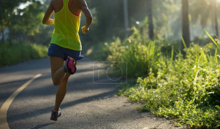 fitness young woman running on morning tropical forest trail