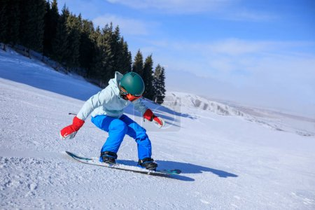 one young woman snowboarding in winter mountains