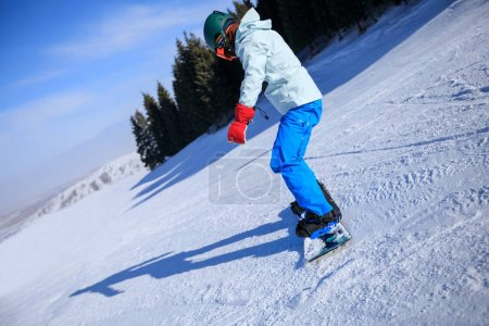 one woman snowboarding in winter mountains