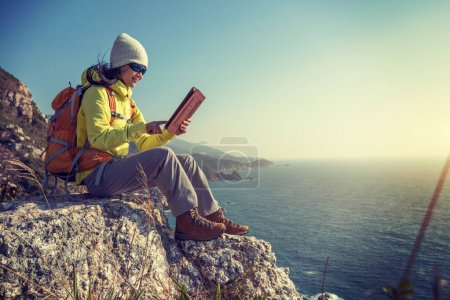 Young Woman Hiker Using digital tablet while hiking at Seaside