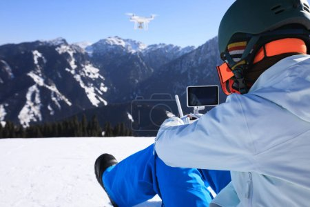 snowboarder with remote control of flying drone on winter mountain top