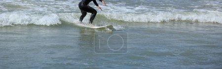 Woman riding wave on surfboard in ocean
