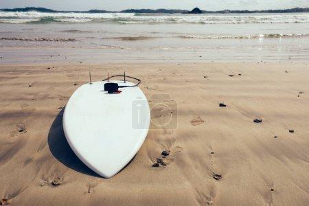White Surfboard with leg leash on beach