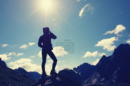 silhouette of woman hiker hiking on sunrise mountain top
