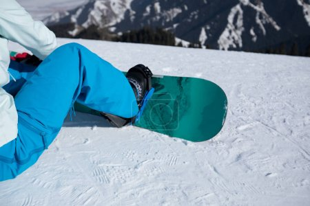 snowboarder sitting on slope while snowboarding on winter mountain top