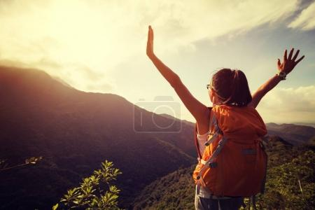 Photo for Happy woman backpacker looking at the mountains with arms outstretched on mountain top during sunrise - Royalty Free Image
