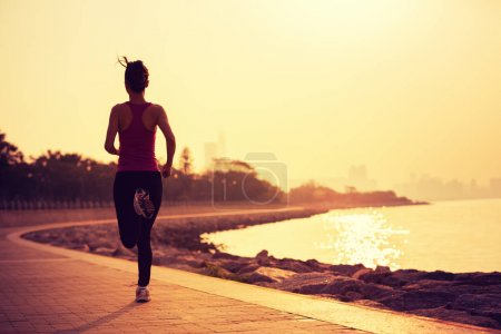 Photo for Sporty fitness woman running on sunrise seaside trail - Royalty Free Image