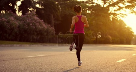 sporty fitness woman running on sunrise trail