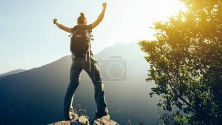successful hiker with arms outstretched on sunrise mountain top