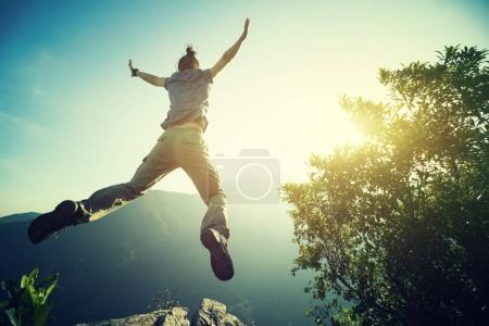hipster woman hiker jumping on mountain
