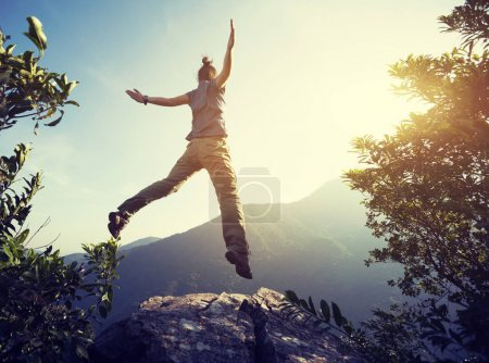 Photo for Hipster woman hiker jumping on mountain - Royalty Free Image